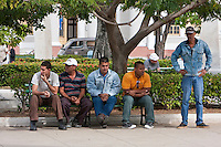 Cuba, Cienfuegos.  Five Men Resting in the park, the Parque Marti.