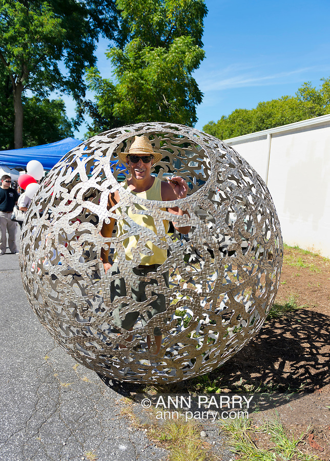 "Huntington, New York, U.S. 24th August 2013. STEVEN ZALUSKI, performance artist, is in his rolling metal sculpture ""Sphere of Hope"" at the art event ""Off the Walls"" Block Party, by SPARKBOOM, a Huntington Arts Council project created to help emerging artists, showcase talents, and help its artistic family network. The sculpture of human shapes welded together has a round opening big enough for a person to enter, Zaluski's studio is in Ronkonkoma."