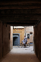 A man on a bicycle is seen passing the in front of an entrance to a doorway with a low timbered ceiling