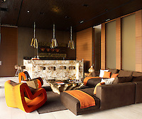 This sitting room in the master suite contrasts with the open feel of the communal spaces, cosseting with slivered wood paneling, bronze-toned curtains, slate, leather and hide.