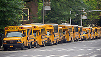 School buses waiting for the dismissal of their passengers are parked outside of an elementary school in the New York neighborhood of Chelsea on Friday, June 26, 2015. Today is the last day of school for New York public school students and is a half-day.  (© Richard B. Levine)