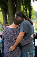 "BURLINGTON, WA - SEPTEMBER 24:  Michelle Kinhart (left) and Mike Berryman hug each other during a community gathering at Maiben Park on September 24, 2016 in Burlington, Washington. ""We could hear the helicopter circling the house all night,"" said Kinhart. ""It was terrifying,"" said Berryman.  Five people were killed last night when a gunman opened fire in the Cascade Mall. (Photo by Karen Ducey/Getty Images)"