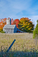 An old barn and silo are surrounded by autumn foliage in Door County, Wisconsin