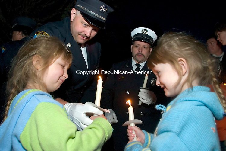 WATERTOWN, CT- 11 SEPT 06- 0911006JT01-<br /> Four-year-old twins Claire and Danielle Demers receive lit candles from their father Scott, as a fellow Watertown firefighter, Mike Knipple, watches during a 9/11 remembrance service sponsored by the town's Ecumenical Council of Churches at the Green on Monday evening. <br /> Josalee Thrift Republican-American