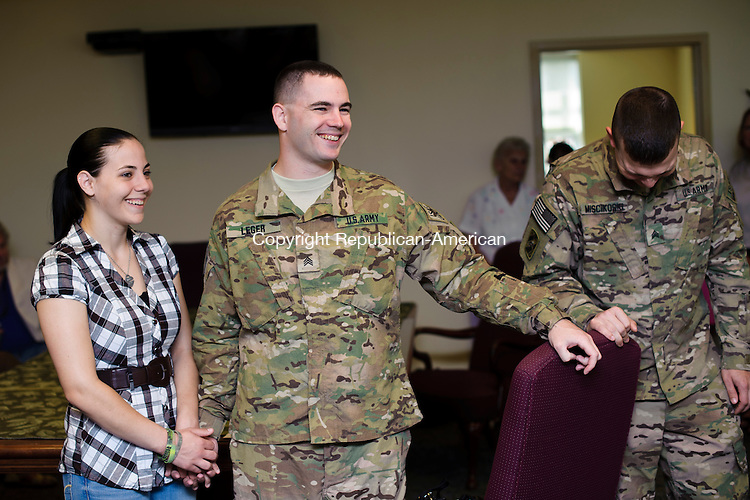 TORRINGTON, CT - 20 August 2013-082013EC01--   Sergeant Tony Leger and his wife Danielle share a laugh during a reception for them at Torrington City Hall Tuesday morning. Next to Leger (R) is Sergeant Jonathan Miscikoski. The two are part of the 1048th Transporation Company of the Connecticut National Guard. The Torrington natives returned home this weekend after working in Afghanistan for 9 months. Erin Covey Republican-American.