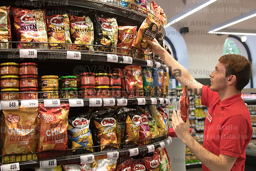 Salesman adjusts chips snack products on the selves before the official opening ceremony of a new Spar food shop in downtown Budapest, Hungary on Aug. 22, 2018. ATTILA VOLGYI
