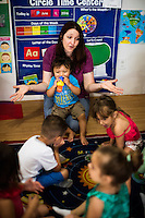 Lora Reyes is a licensed family childcare educator in Westfield, Mass., where she operates the daycare Lora's Little Ones out of her home on Thurs., June 2, 2016. Here she leads children in a welcome activity before breakfast. Today she was in charge of 7 children, aged 14 months to 5 years old, handling meals, playtime, and educational activities throughout the day, starting about 7am and going until 4:30pm. She uses the Mother Goose Time curriculum throughout the day. Reyes is currently pursuing an undergraduate degree in Psychology at Holyoke Community College. She started 2 years ago after earning a Child Development Associate certification.
