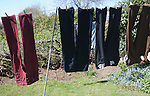 Trousers of different colours hanging from washing line, UK