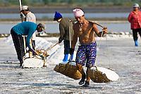 Man carries farmed salt in traditional shoulder baskets, Bangkok, Thailand