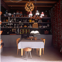 A country kitchen with a wooden table with a blue check tablecloth. Kitchenware is stored on shelves against one wall. A chandelier with fringed shades hangs above the table.