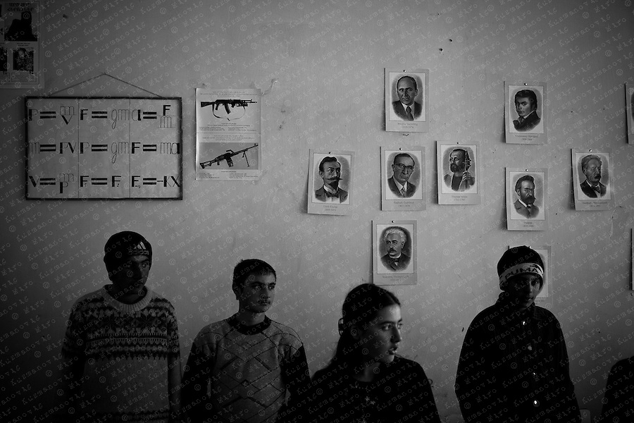 A AK-47 Kalashnikov poster is seen on the wall as Pupils stand in their classroom.