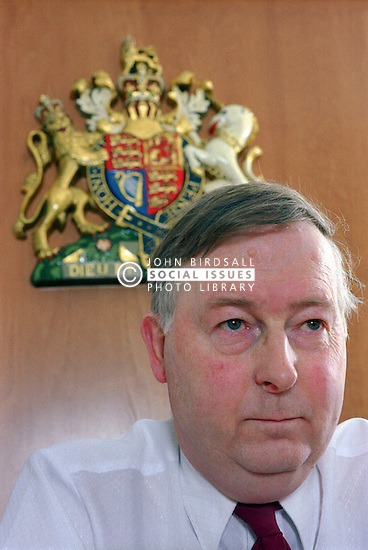 Portrait of male magistrate listening to case of young offender in youth court,
