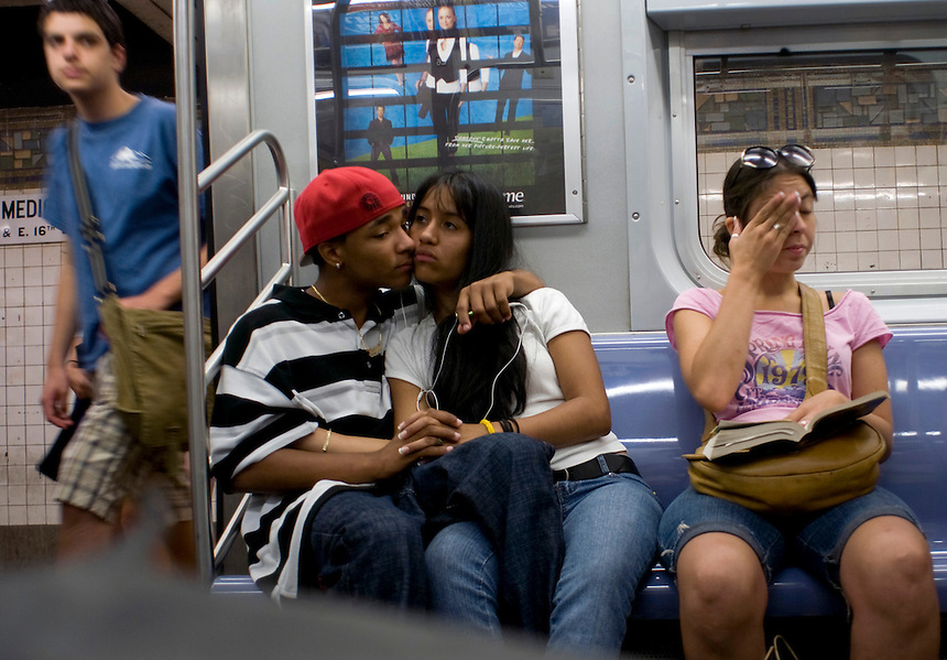 A young couple cuddle and kiss on the subway. Subway riders. Street photography in NY August 5, 2007
