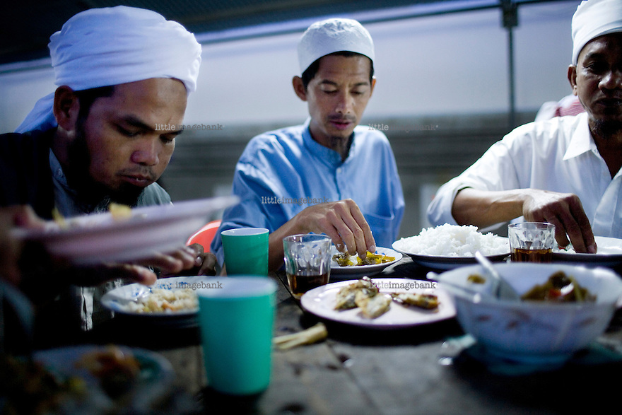 During the holy month of ramadan, in the backyard of the central mosque of Pattani, men are eating their supper before their evening prayer. Thailand is struggling to keep up appearances as the land of smiles has to face up to its troubled south. Since 2004 more than 3500 people have been killed and 4000 wounded in a war we never hear about. In the early hours of January 4th 2004 more than 50 armed men stormed a army weapons depot in Narathiwat taking assault rifles, machine guns, rocket launchers, pistols, rocket-propelled grenades and other ammunition. Arsonists simultaneously attacked 20 schools and three police posts elsewhere in Narathiwat. The raid marked the start of the deadliest period of armed conflict in the century-long insurgency. Despite some 30,000 Thai troops being deployed in the region, the shootings, grenade attacks and car bombings happen almost daily, with 90 per cent of those killed being civilians. 19.09.07. Photo: Christopher Olssøn