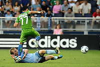 Seth Sinovic (16) defender Sporting KC slide tackles Fredy Montero (17) ) forward Seattle Sounders..... Sporting Kansas City were defeated 1-2 by Seattle Sounders at LIVESTRONG Sporting Park, Kansas City, Kansas.
