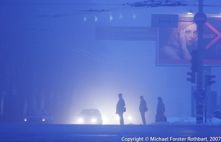 In the pre-dawn fog, commuters wait outside the Pechersk Metro station in Kyiv, Ukraine, 65 miles from Chernobyl. Radiation from Chernobyl dispersed erratically, based on winds and rainfall. Officially, the radiation leapfrogged over Kyiv and did not affect the capital. However, some Kyiv residents now question whether this is really true.  <br /> ------------------- <br /> This photograph is part of Michael Forster Rothbart's After Chernobyl documentary photography project.<br /> © Michael Forster Rothbart 2007-2010.<br /> www.afterchernobyl.com<br /> www.mfrphoto.com <br /> 607-267-4893 o 607-432-5984<br /> 5 Draper St, Oneonta, NY 13820<br /> 86 Three Mile Pond Rd, Vassalboro, ME 04989<br /> info@mfrphoto.com<br /> Photo by: Michael Forster Rothbart<br /> Date:  2/2007    File#:  Canon 20D digital camera frame 8543 <br /> ------------------- <br /> Original caption: .Photo title:.Winter twilight in Pechersk, Kyiv..Caption:.In the pre-dawn fog, commuters wait to cross the street outside the Pechersk Metro station in Kyiv, 65 miles from Chernobyl...Radiation from Chernobyl dispersed erratically, based on winds and rainfall. Officially, the radiation leapfrogged over Kyiv and did not affect the capital. However, many Kyiv residents question whether this is really true. ..Quote: none.-------------------.