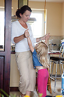 Polish mom playing with her daughter age 4 in her kitchen. Zawady Central Poland