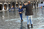 A lady poses with boots at flooded St Mark's square during an acqua alta (high-water). The Acqua Alta, a convergence of high tides and a strong sirocco, reached 125 centimetres in Venice, on November 20, 2013.  <br /> <br /> &copy; Pierre Teyssot