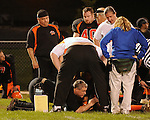 In an unusual gesture, Cannons Coach Mike Kraus who is also an.EMT, comforts an injured player on the opposing Valley Tigers team..Play was haulted for more than an hour while a State Police helicopter.has summoned to the Taneytown stadium.
