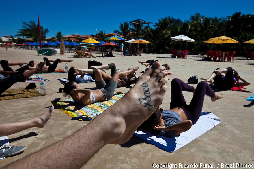 Young people practicing yoga at Geriba beach, Armacao de Buzios, Rio de Janeiro State, Brazil - Peace tattoed on foot - physical, mental, and spiritual practice with a view to attain a state of peace and wellness.