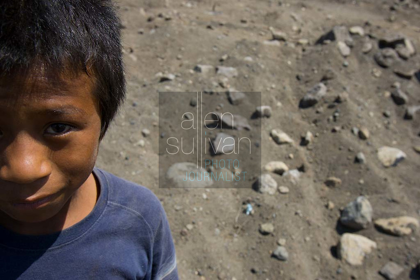 Diego Elias Mendoza Santos, 12, also known as Rambo, stands at the spot of his former home in an area of Panabaj, Guatemala on Tuesday, March 20, 2007. A deadly mudslide here was spawned by rains associated with Hurricane Stan in October 2005. Initially, up to 500 Tzujutil Maya villagers were believed to have been killed by the mudslide, which essentially  wiped away the town. Rambo lost his parents and a sister and brother. Forensic anthropologists from the Fundación de Antropología Forense de Guatemala have been working to unearth the bodies of the missing and have recovered more than 100. They have also found the number of missing to be lower than originally thought, after many people were located in shelters or living in other towns after the disaster.