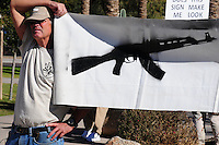 "Phoenix, Arizona. January 19, 2013 - A demonstrator holds a banner during Saturday's rally in Phoenix to oppose to proposed changes in gun control laws. As President Barack Obama proposed new gun regulations last week, gun owners demonstrated against it with national ""Guns Across America"" rallies to defend the Second Amendment. Dozens showed up at the Arizona State Capitol, many of them carrying weapons. Photo by Eduardo Barraza © 2013"