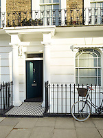 A bicycle is propped against the black-painted railings infront of this mid-terrace Victorian house in London