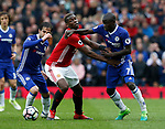 Paul Pogba of Manchester United tackled by Cesc Fabregas and Ngolo Kante of Chelsea during the English Premier League match at Old Trafford Stadium, Manchester. Picture date: April 16th 2017. Pic credit should read: Simon Bellis/Sportimage