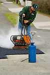 construction workers uses a plate compactor on an asphalt patch