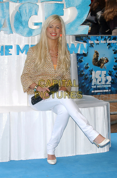 """CHANTELLE HOUGHTON.attending the Film Premiere of """"Ice Age 2: The Meltdown"""" Empire Leicester Square, London, England, .3rd April 2006..full length peach orange earrings lipstick lipgloss woven jacket white skinny jeans shoes sitting black clutch bag.Ref: BEL.www.capitalpictures.com.sales@capitalpictures.com.©Tom Belcher/Capital Pictures."""