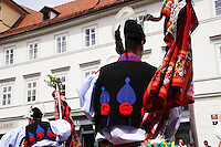 The Ride of the Kings takes place during the spring, as a part of the Pentecost traditions, in the towns of Hluk and Kunovice and the villages of Skoronice and Vlčnov. A group of young men ride through a Prague in a ceremonial procession. The ride is headed by chanters, followed by pageboys with unsheathed sabres who guard the King – a young boy with his face partially covered, holding a rose in his mouth – and the rest of the royal cavalcade. The King and pageboys are dressed in women's ceremonial costumes, while the other riders are dressed as men. The entourage rides on decorated horses, stopping to chant short rhymes that comment humorously on the character and conduct of spectators. The chanters receive donations for their performance, placed either in a money box or directly into the riders' boots. The King's retinue returns home after a few hours of riding, and celebrates in the evening at the house of the King with a small feast, music and dancing. The practices and responsibilities of the Ride of the Kings are transmitted from generation to generation. The traditional paper decorations for the horses and the ceremonial costumes, in particular, are made by women and girls familiar with the processes, colour patterns and shapes specific to each village.