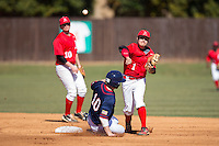 Ryan Allen (1) of the Belmont Abbey Crusaders turns a double play as Ryan McMillen (10) of the Shippensburg Raiders slides into second base at Abbey Yard on February 8, 2015 in Belmont, North Carolina.  The Raiders defeated the Crusaders 14-0.  (Brian Westerholt/Four Seam Images)