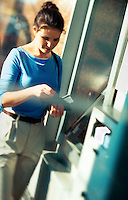 Blurred image of a woman at an ATM cash machine.