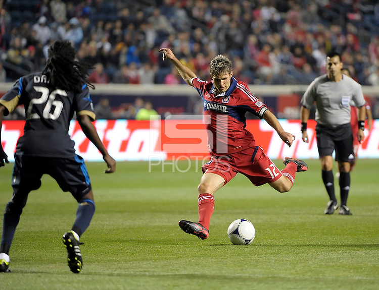 Chicago Fire midfielder Logan Pause (12) shoots in front of Philadelphia Union midfielder Keon Daniel (26).  The Chicago Fire defeated the Philadelphia Union 1-0 at Toyota Park in Bridgeview, IL on March 24, 2012.