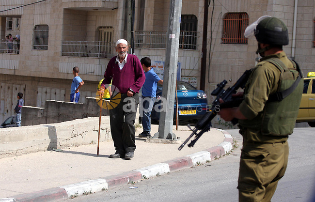 Israeli border guards stand guard near Palestinian civilians during a raid in the West Bank city of Ramallah on May 30, 2011. Five Palestinians were arrest, three from the village of Amrine, near the northern West Bank city of Nablus and two others, from the area around Ramallah, Palestinian security sources said.Photo by Issam Rimawi