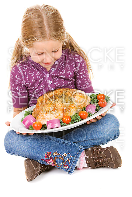 Little girl in casual wear holding turkey and pumpkins for Thanksgiving.