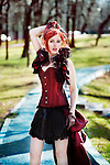 Girl in red Victorian corset with ruffle, standing outdoors on a path in park