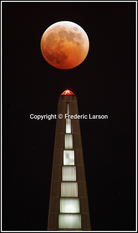 A full eclipse of the moon, like an evil pumpkin, tops San Francisco Transamerica Pyramid in San Francisco, California..