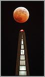 A full eclipse of the moon, like an evil pumpkin, tops San Francisco Transamerica Pyramid in San Francisco, California..