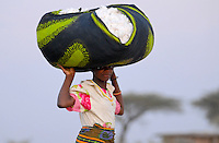 Tanzania, organic cotton project biore of swiss yarn trader Remei AG in Meatu district, women carry harvested bio cotton on the head to the village / Tansania , biore Biobaumwolle Projekt der Schweizer Remei AG in Meatu, Frauen tragen geerntete Biobaumwolle auf dem Kopf ins Dorf