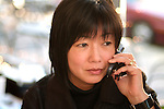 Asian woman on cell phone, concerned