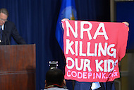 December 21, 2012  (Washington, DC)  A protestor from Codepink.org interrupts NRA President Wayne Lapierre as he delivers prepared remarks during a news conference in Washington.  (Photo by Don Baxter/Media Images International)