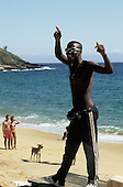 Buzios, Rio de Janeiro State, Brazil. Black man with sunglasses and walkman on the beach; couple walking a dog.
