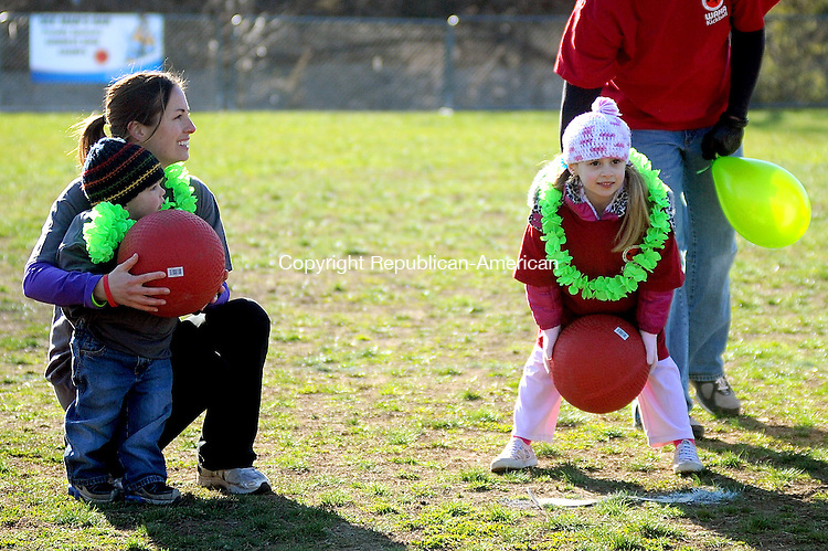 "NAUGATUCK. CT, 30 MARCH  2012-033012JS01-Juliana Beloin, 6, of Wolcott, right, of ""Team Juliana"" tosses out the ceremonial first ball as 2 year-old Sammy Foran  of West Hartford and his mother Delia Foran, left, of ""Team Sammy"" wait for their turn during the opening ceremonies of a three-day, 60-hour kickball game Friday at Linden Park in Naugatuck. Money raised from the event withh go to CureSearch for Children's Cancer. As of Friday monring the event raised more than $38,000. .Jim Shannon Republican-American"