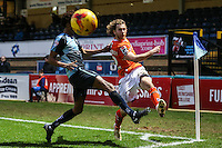 Craig Mackail-Smith of Luton Town (right) crosses the ball under pressure from Sido Jombati of Wycombe Wanderers (left) during the Sky Bet League 2 match between Wycombe Wanderers and Luton Town at Adams Park, High Wycombe, England on 6 February 2016. Photo by David Horn.
