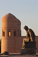 Detail of Statue of Muhammad ibn Musa Al-Khwarizmi (c.780-c.850), astronomer and mathematician, with main gate of Ichan-Kala, Ota Darvoza (Father Gate), in the background, Khiva, Uzbekistan, pictured on July 5, 2010, in the afternoon. Khiva's old city, Ichan Kala, is surrounded by 2.2 kilometres of crenellated and bastioned city walls. Some sections may be 5th century, but the strongest sections were built 1686-88 by Arang Khan. The main gate today is the restored western Ota Darvoza (Father Gate). Khiva, ancient and remote, is the most intact Silk Road city. Ichan Kala, its old town, was the first site in Uzbekistan to become a World Heritage Site(1991). Picture by Manuel Cohen.