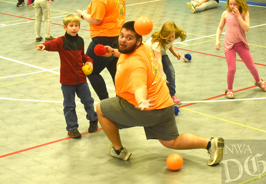 NWA Democrat-Gazette/FLIP PUTTHOFF <br /> EYE ON THE SPRING BREAK BALL<br /> Juan Jacobo, with the Rogers Activity Center staff, makes an acrobatic catch Wednesday March 20 2019 during a game of spider ball at the center. The game is like dodge ball only no one is out when they're hit, Jacobo said, and lots of balls are used. The game was part of spring break activities at the center, 315 W. Olive St. Bowling at Rogers Bowling Center is the center's main spring break event today.