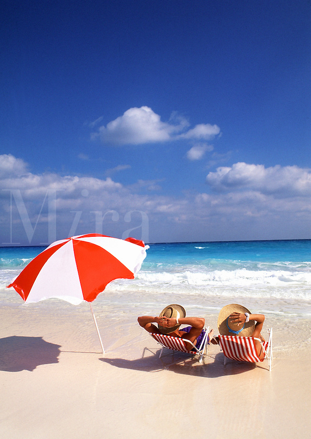 Couple relaxing in beach chairs with umbrella