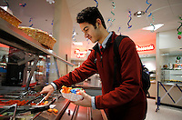 NWA Media/DAVID GOTTSCHALK - 12/19/14 - Herminio (cq) Cortes, a senior at Rogers High School, puts carrots on his plate from the Garden Bar available at the cafeteria at the school Friday December 19, 2014.