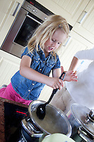 Polish mom watching daughter age 32 and 4 cook stirring at the kitchen stove. Zawady Central Poland